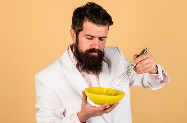Homem barbudo preparando ovos para o café da manhã, batendo ovo em uma tigela para cozinhar omelete ou massa, utensílios de cozinha, cozinha e conceito de cozinha,