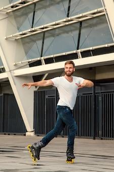 Homem barbudo profissional em patins em pé na construção de plano de fundo. jovem apto homem com camisetas brancas e jeans de patins, andando ao ar livre depois da chuva.
