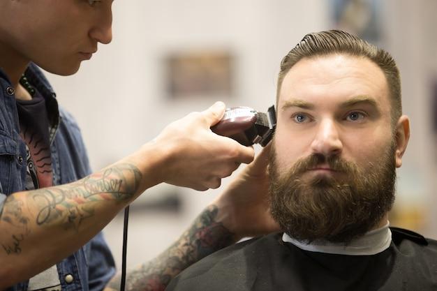Homem barbudo que corta cabelo na barbearia