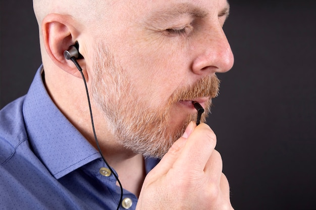 Homem barbudo quer ouvir música com fones de ouvido a vácuo