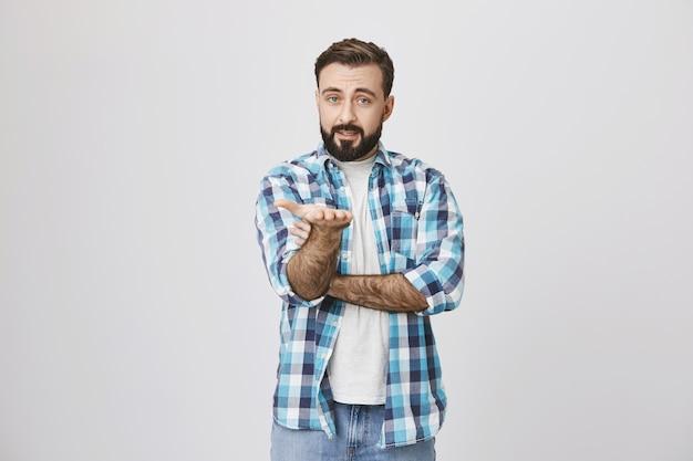 Homem barbudo questionado mostrando algo na mão