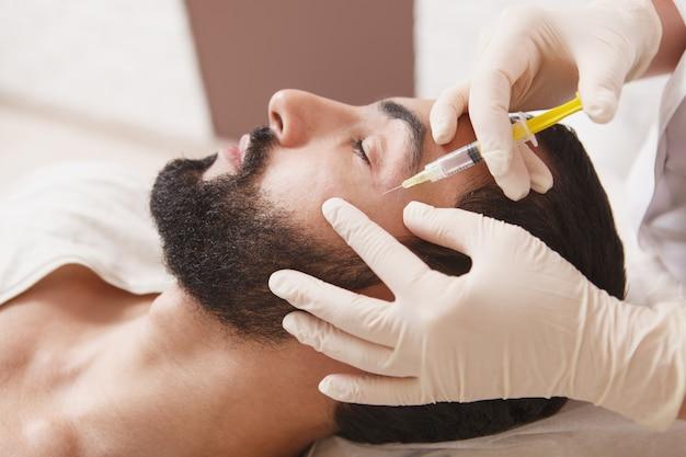 Homem barbudo recebendo tratamento anti-rugas de preenchimento facial com esteticista