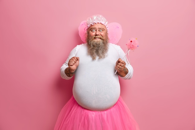 Homem barbudo rechonchudo tem imagem de fada mágica, fecha o punho, feliz com sua habilidade de fazer as coisas desaparecerem, finge ser um ser sobrenatural, brinca com as crianças na festa