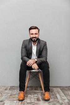 Homem barbudo relaxado de corpo inteiro, sentado na cadeira no escritório e sorrindo para a câmera isolada sobre cinza