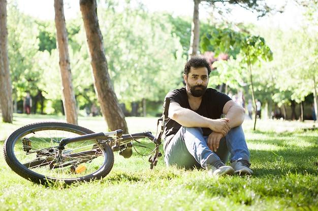 Homem barbudo relaxando no parque na grama ao lado de sua bicicleta