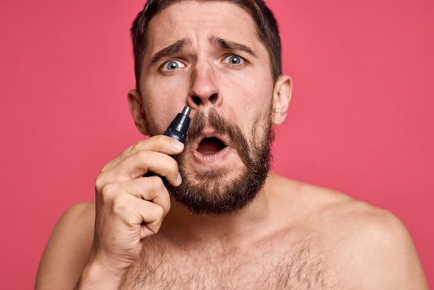 Homem barbudo remove o cabelo do nariz