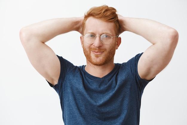 Homem barbudo ruivo bonito e atrevido de óculos, segurando as mãos atrás da cabeça relaxado, descansando
