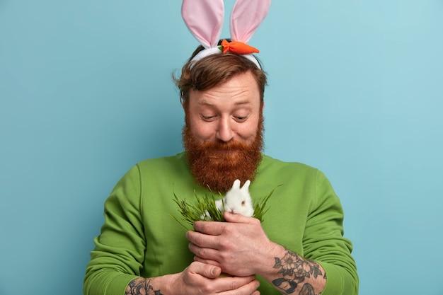 Homem barbudo ruivo com orelhas de coelho alimentando coelho branco fofinho