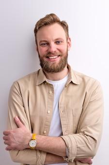 Homem barbudo ruivo em roupa casual sorrindo para a câmera e posando com os braços cruzados