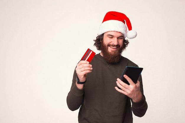 Homem barbudo satisfeito está usando o cartão do banco, fazendo pedidos online e olhando para o tablet.