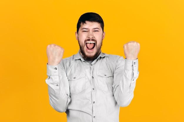 Homem barbudo se alegra com vitória, punhos cerrados, imagem sobre parede laranja
