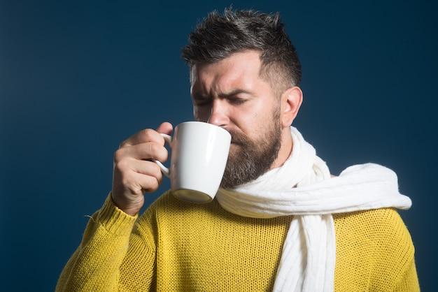 Homem barbudo se aquecendo com chá quente no inverno. homem bebe bebida quente. tempo frio. bebidas quentes.