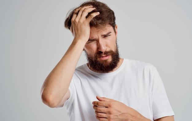 Homem barbudo segurando a cabeça descontente com distúrbio de saúde