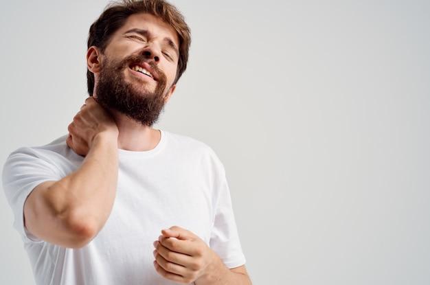 Homem barbudo segurando artrite no pescoço, problemas de saúde, estúdio de tratamento
