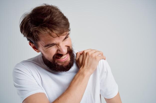 Homem barbudo segurando artrite no pescoço, problemas de saúde, luz de fundo
