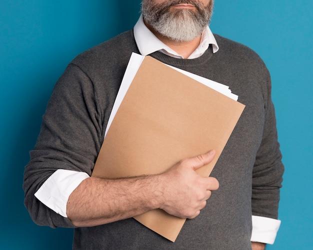 Homem barbudo segurando documentos comerciais