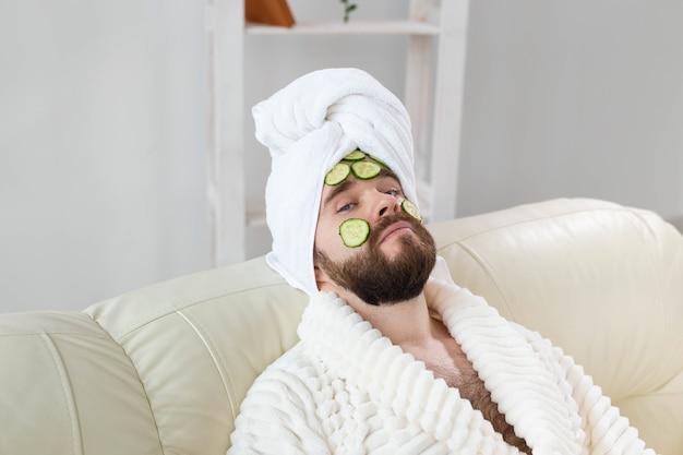 Homem barbudo segurando fatias de pepino no rosto. spa em casa, corpo e pele para o conceito masculino.