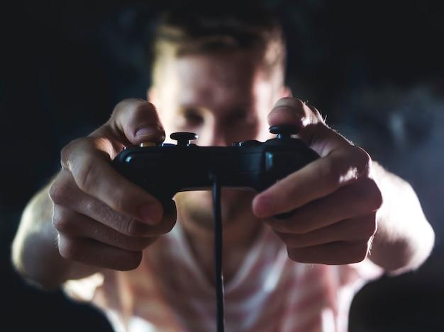 Homem barbudo segurando o controlador de joystick de videogame nas mãos na frente do corpo em casa durante a noite.