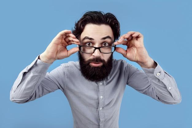 Homem barbudo segurando óculos com os olhos bem abertos