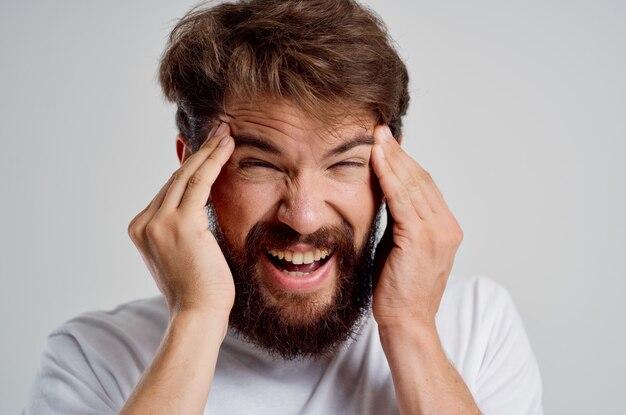 Homem barbudo segurando suas emoções de estresse de dor de cabeça fundo isolado