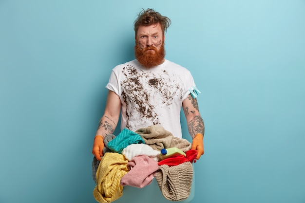 Homem barbudo segurando um cesto de roupa suja, sobrecarregado com as tarefas domésticas