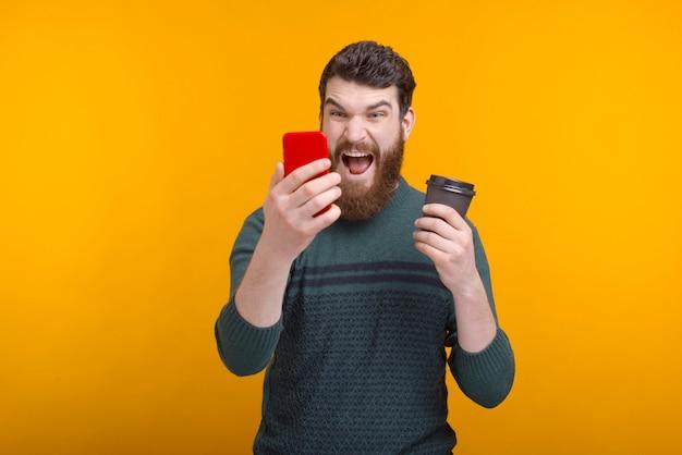 Homem barbudo segurando um copo de papel preto está gritando com seu telefone.