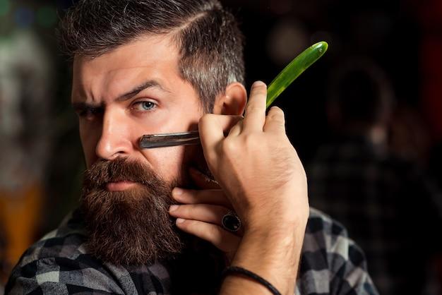 Homem barbudo segurando uma navalha na bochecha