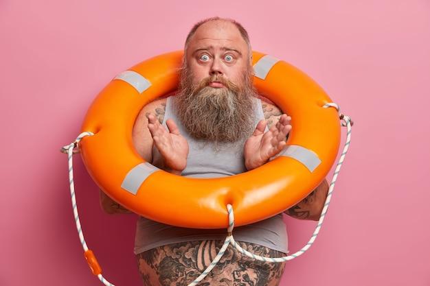 Homem barbudo sem noção com barriga gorda espalha as palmas das mãos e se sente confuso, carrega o anel da vida, olhares esbugalhados, tem poses de excesso de peso contra uma parede rosada
