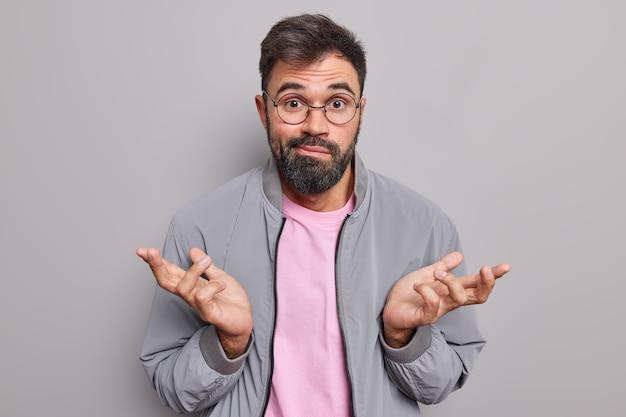 Homem barbudo sem noção encolhe os ombros parece perplexo e inconsciente dizer que não entendo
