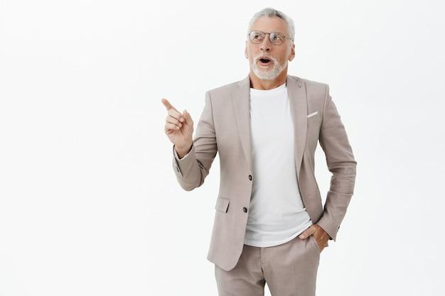 Homem barbudo sênior animado e satisfeito em um terno apontando e olhando para o canto superior esquerdo