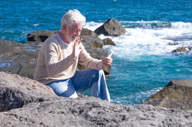 Homem barbudo sênior, apreciando a excursão no mar, sentado usando um telefone celular. horizonte sobre a água