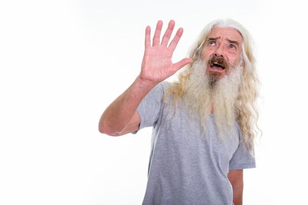 Homem barbudo sênior assustado mostrando a mão parada