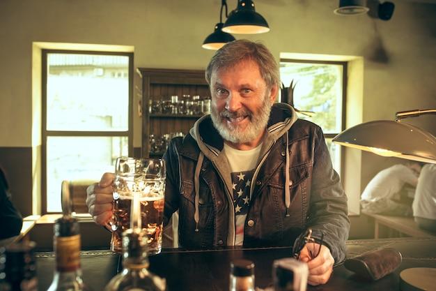 Homem barbudo sênior bebendo álcool em um bar e assistindo a um programa de esporte na tv. aproveitando minha cerveja favorita. homem com uma caneca de cerveja, sentado à mesa. fã de futebol ou esporte. conceito de emoções humanas