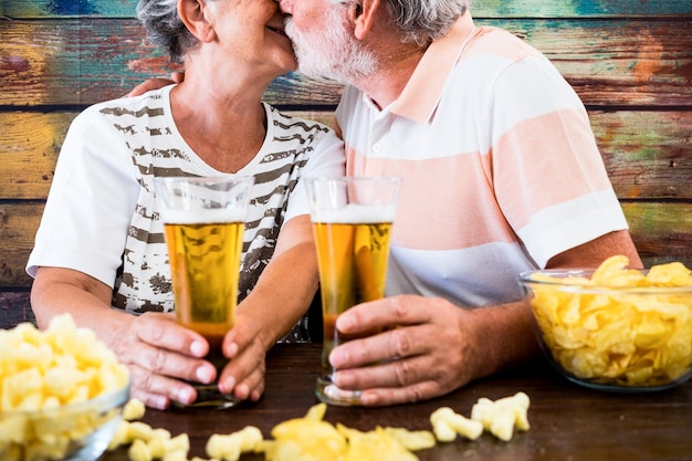 Homem barbudo sênior beija a esposa sentada em um bar em uma mesa de madeira brindando com copos de cerveja
