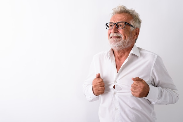 Homem barbudo sênior estressado pensando enquanto rasga a camisa e usa óculos em branco