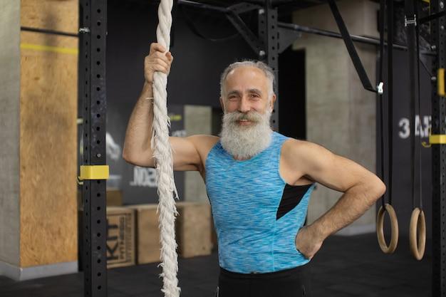Homem barbudo sênior exercitando com cordas no ginásio. atividade física e estilo de vida saudável.