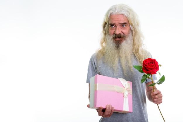 Homem barbudo sênior feliz e pensativo sorrindo enquanto segura o presente