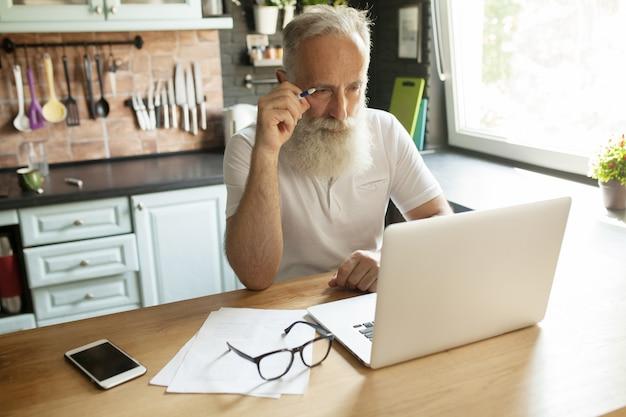 Homem barbudo sênior na sala de estar usando o computador portátil