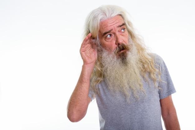 Homem barbudo sênior ouvindo enquanto pensa