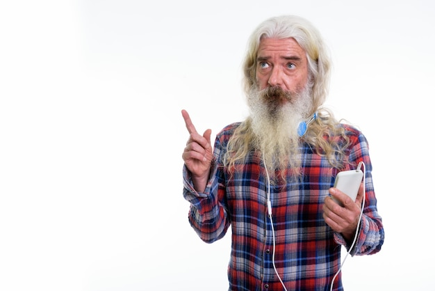 Homem barbudo sênior pensativo usando fones de ouvido no pescoço