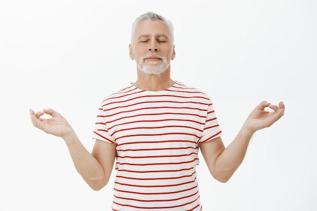 Homem barbudo sênior relaxado e paciente meditando, praticando ioga
