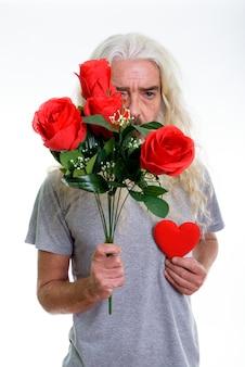 Homem barbudo sênior se escondendo atrás de rosas vermelhas