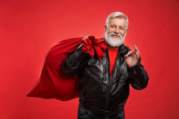 Homem barbudo sênior segurando uma sacola de papai noel e mostrando sinal de ok