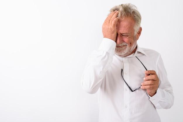 Homem barbudo sênior triste enxugando as lágrimas enquanto segura os óculos no branco
