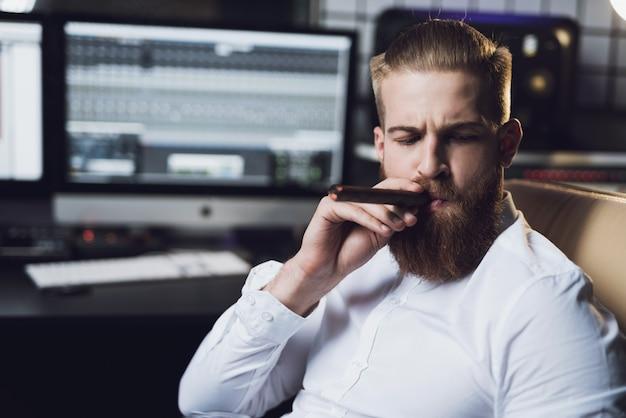 Homem barbudo senta-se no estúdio e fuma charuto.