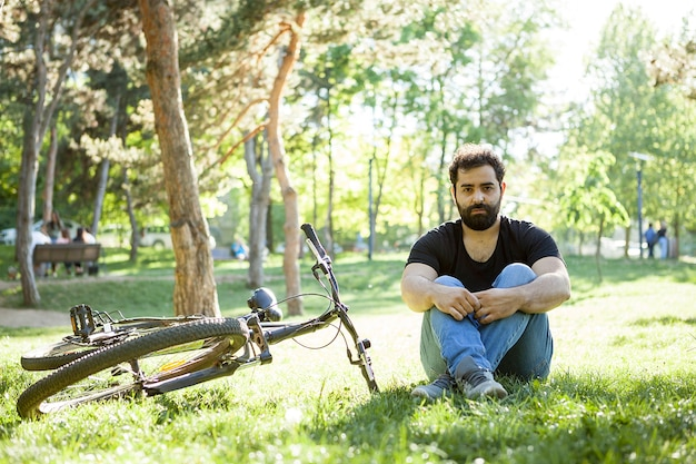 Homem barbudo sentado ao lado de sua bicicleta no chão do parque