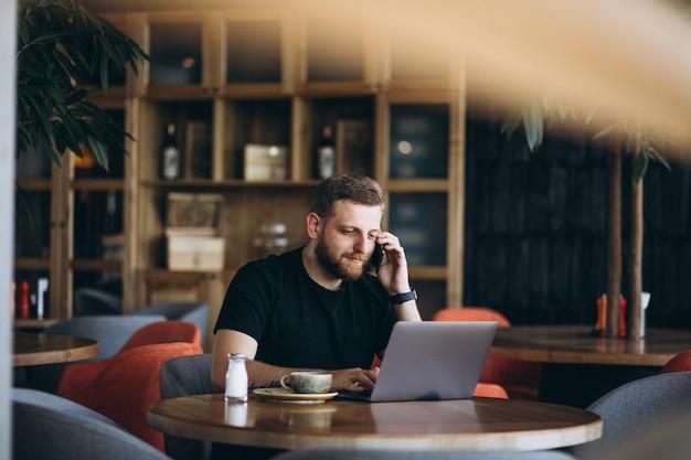 Homem barbudo sentado em um café, bebendo café e trabalhando em um computador