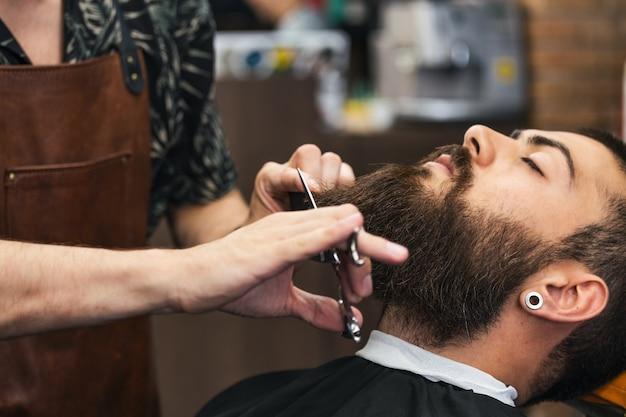 Homem barbudo sentado em uma poltrona em uma barbearia enquanto cabeleireiro tropeça em sua barba com uma tesoura