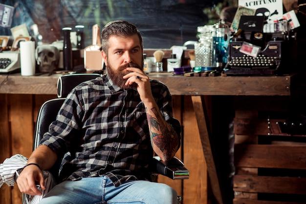 Homem barbudo sentado na cadeira da barbearia