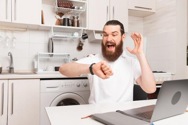 Homem barbudo sentado na cozinha está olhando para o relógio.